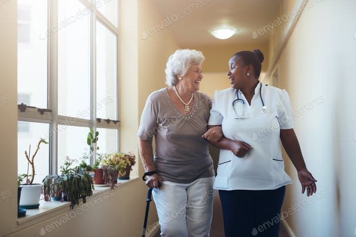 Smiling healthcare worker and senior woman walking together