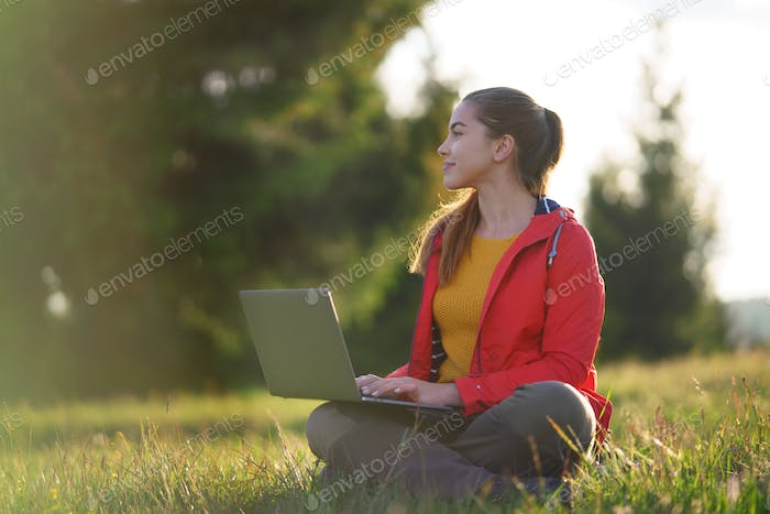 Happy young woman using laptop in summer nature, outdoor office concept