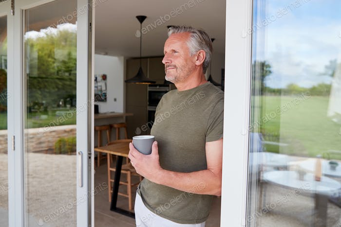 Senior Man Standing And Looking Out Of Kitchen Door Drinking Coffee