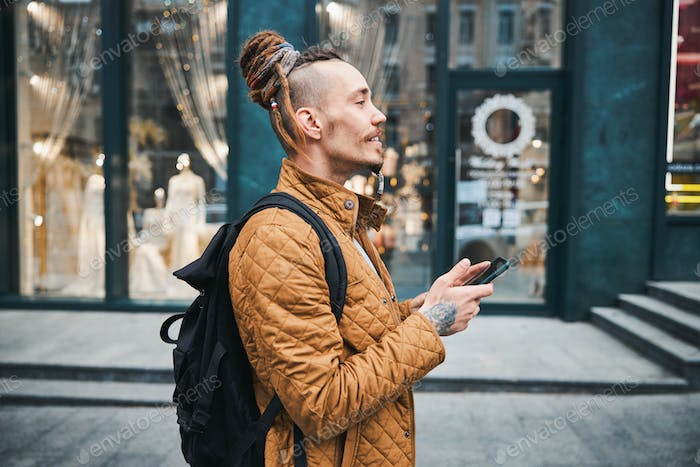 Profile of handsome man with dreadlocks in the street