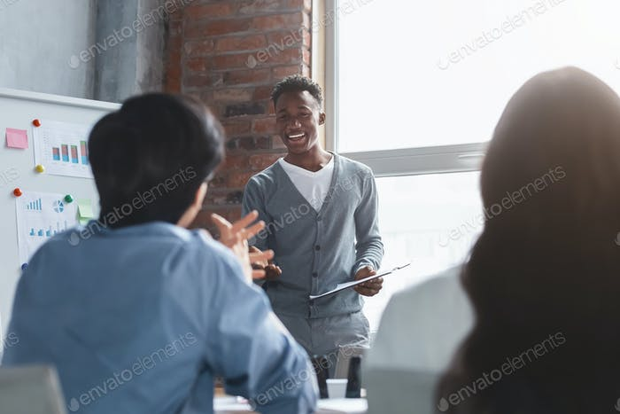 Cheerful black employee talking to colleagues while presentation
