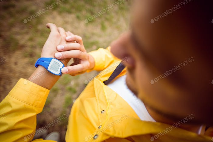 Man using his smartwatch on a hike in the countryside