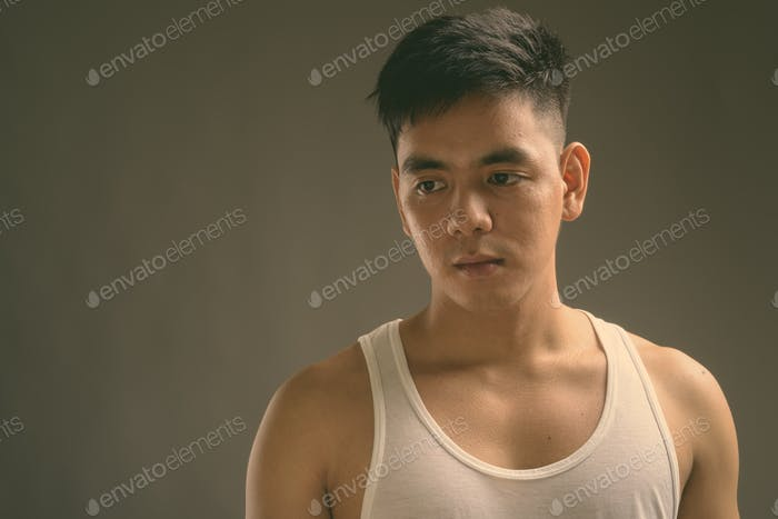 Young handsome Asian man wearing tank top against gray background