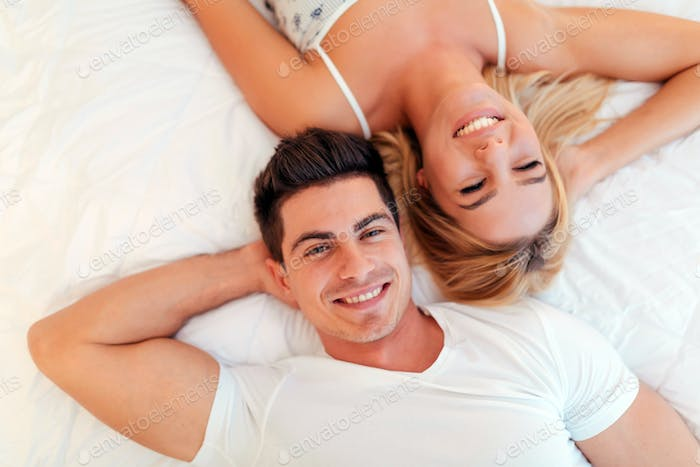 Happy married couple relaxing lying on bed