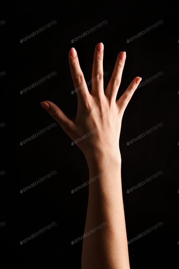 Female hand shows number five isolated at black