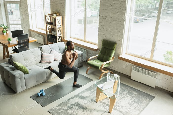 Young african-american man training at home during quarantine of coronavirus outbreak, doinc