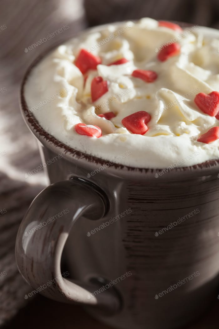 cup of coffee with whipped cream and red hearts