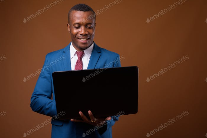Studio shot of young African businessman against brown backgroun
