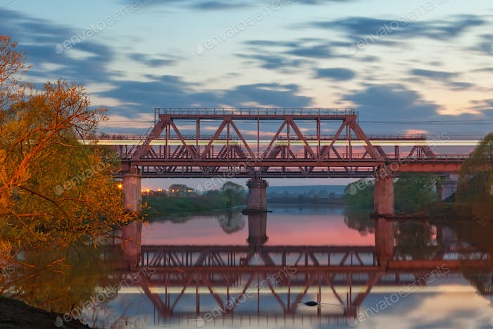 Railway bridge over the river at sunset