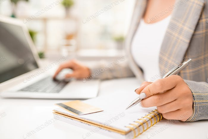 Hand of businesswoman with pen over blank page of notebook with plastic card
