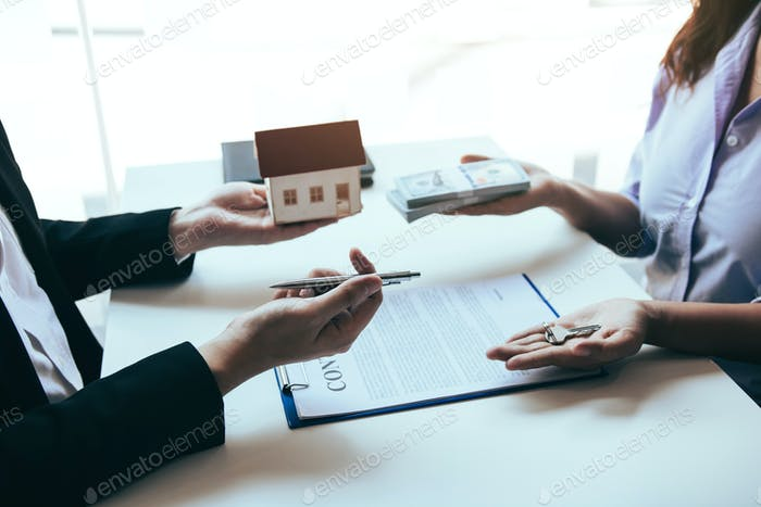 Hand of real estate agent passes the key to new homeowners in office with buyer house concept.