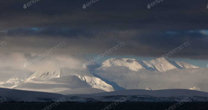 Antarctica. Snow covered peaks with low cloud.