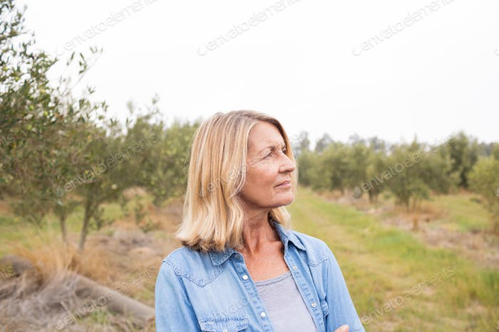 Thoughtful woman standing in olive field
