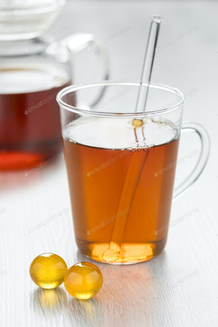 Glass of tea with yellow honey pearls