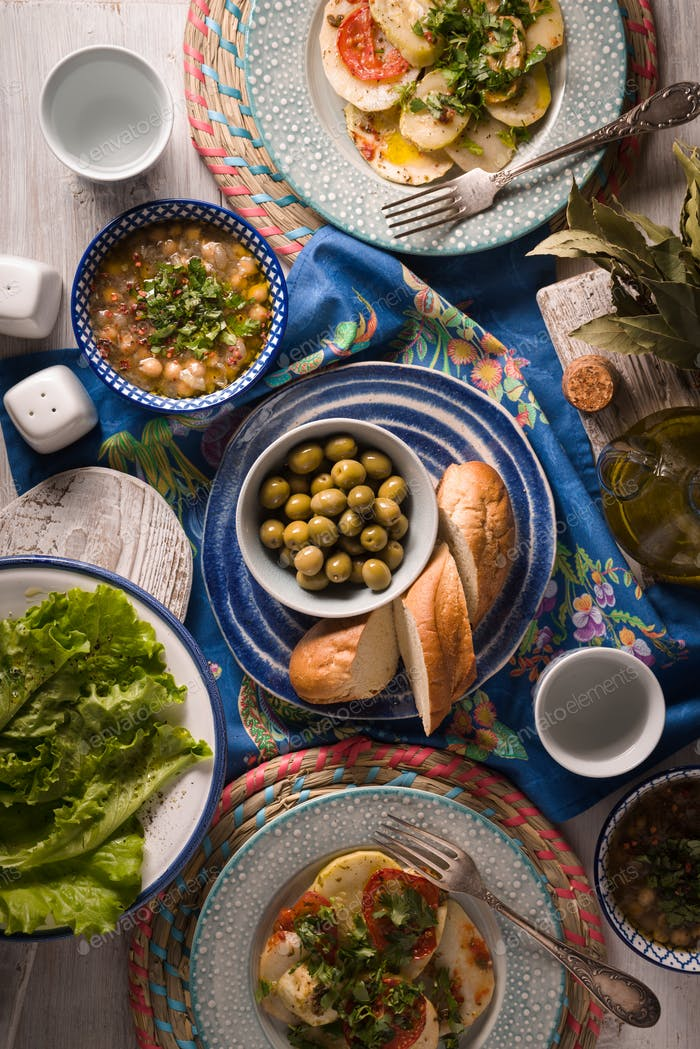 Greek dinner with traditional dishes on the  white table vertical