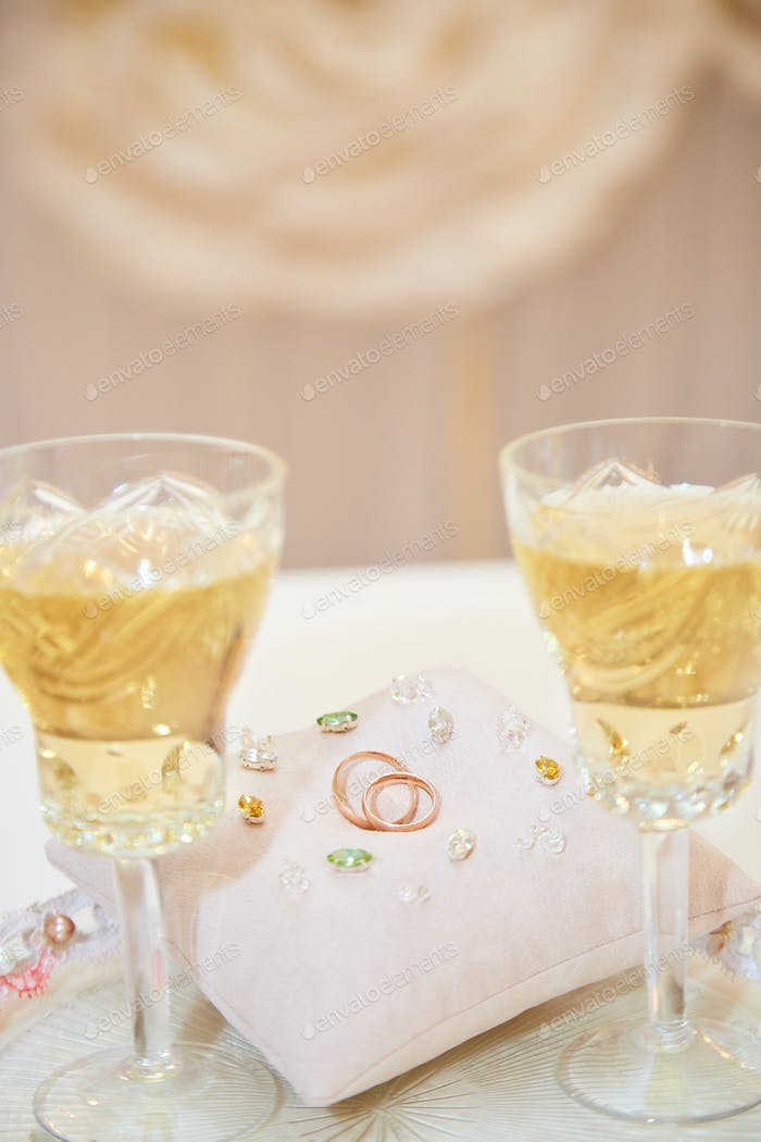 Two glasses of a champagne and pillow with wedding rings