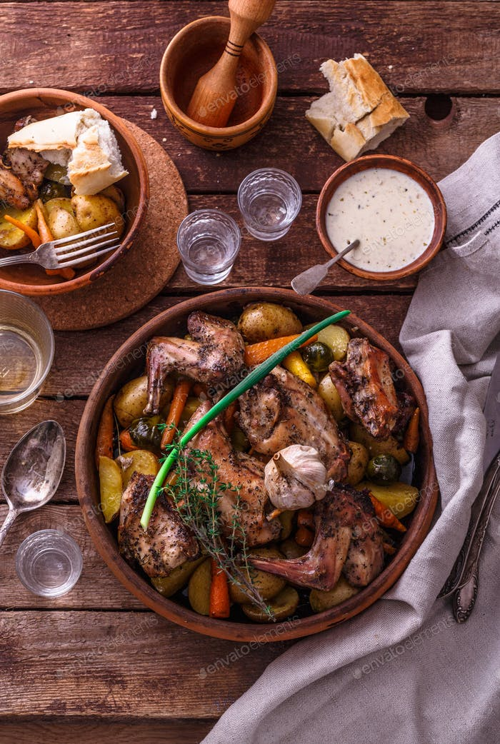 Oven baked rabbit with potato and carrots, top view
