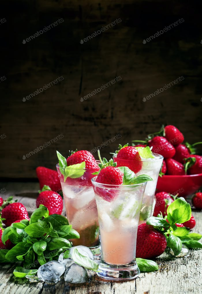 Alcoholic cocktail with Cachaca, cranberry drink, strawberries, lime juice, green basil