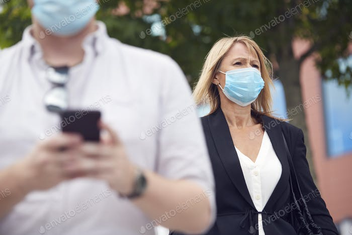Mature Businesswoman Wearing PPE Face Mask Walking Outdoors In Street During Health Pandemic