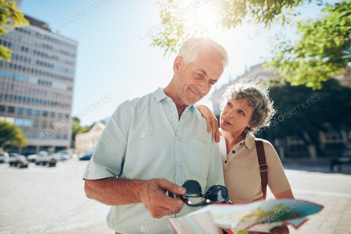 Senior couple using road map in a foreign city