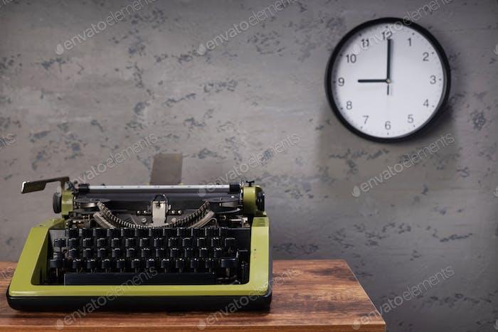 старая пишущая машинка на деревянном столе возле стены