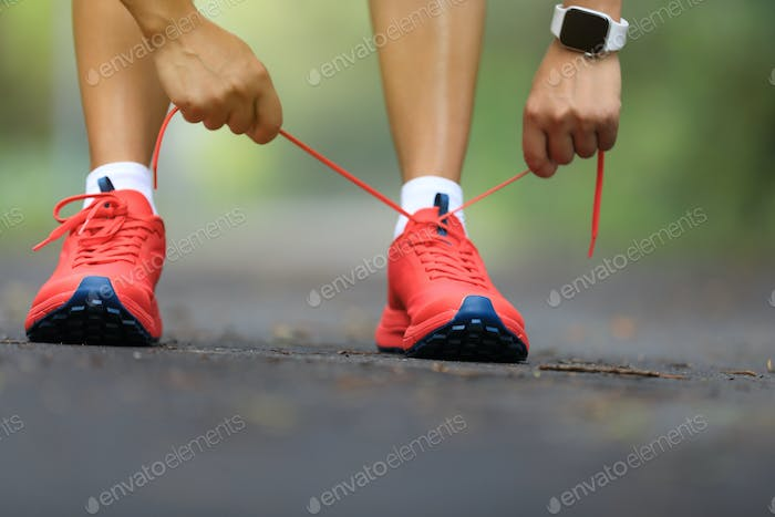Runner tying shoelace on summer forest trail