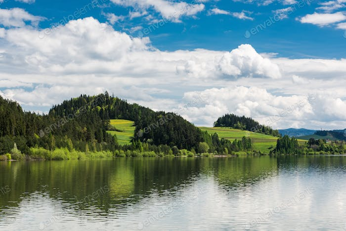 Serene landscape with green hills at lake, summer sunny day with