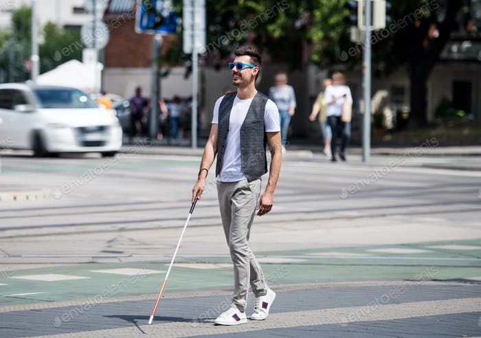 Young blind man with white cane walking across the street in city