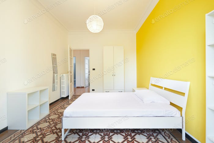 Renovated bedroom in apartment for rent with white and yellow wall