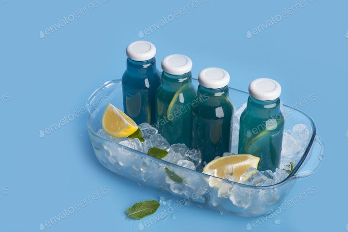 Cold blue organic cocktail with fresh lemons on blue background
