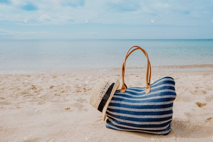 Blue beach bag with hat on the sandy beach with the blue sky background