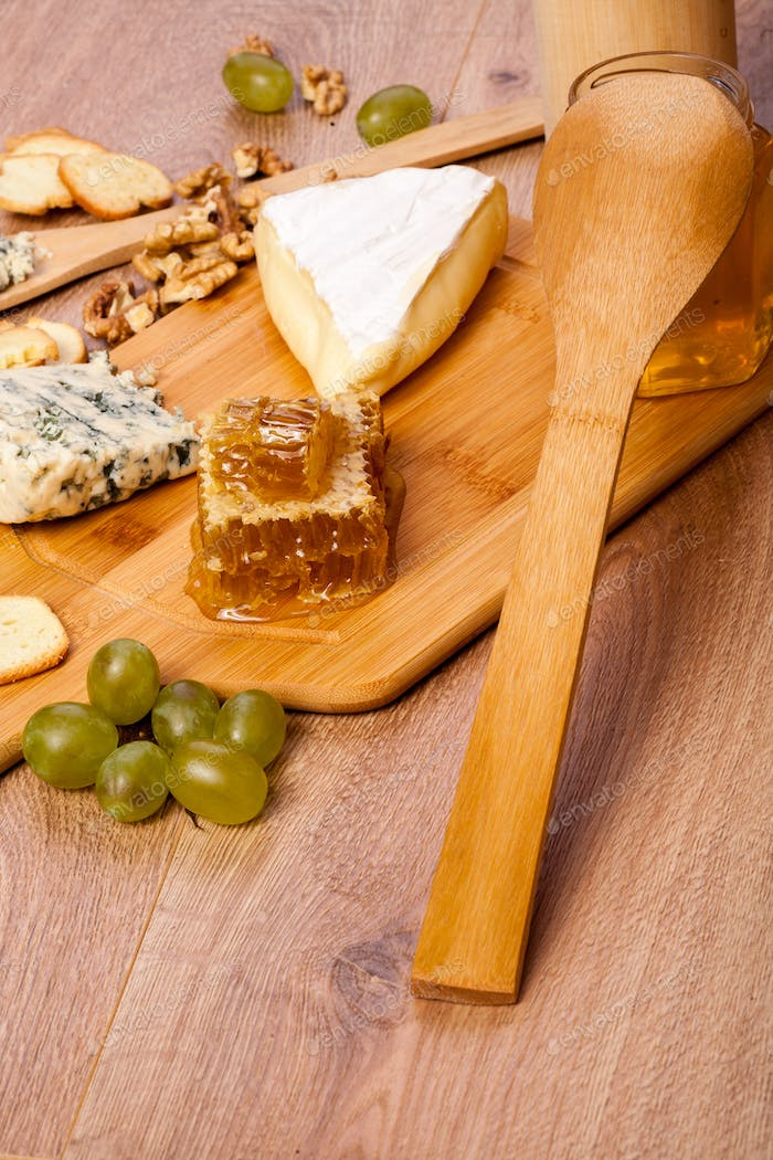 Cheese, nuts and honey on wooden background