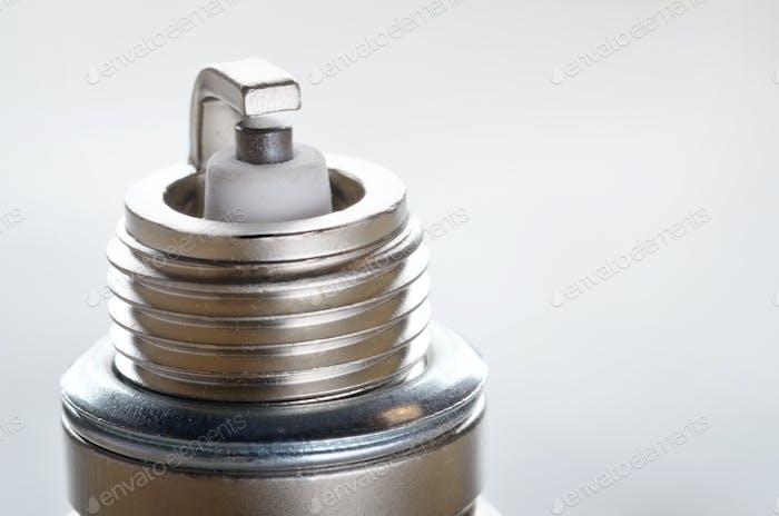 Nahaufnahme der neuen Zündkerze für Verbrennungsmotor auf Metallhintergrund. Platz für Text