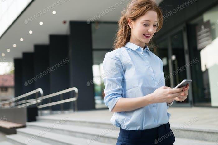 Attraktive junge Geschäftsfrau mit Handy außerhalb