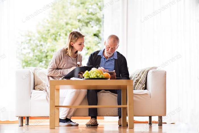 Health visitor and a senior man with tablet during home visit. Foto ...