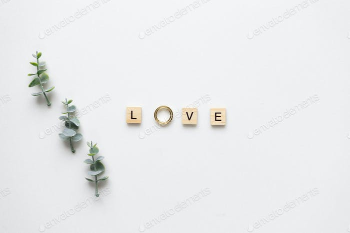 Wooden letters and wedding rings spelling love, with candies and