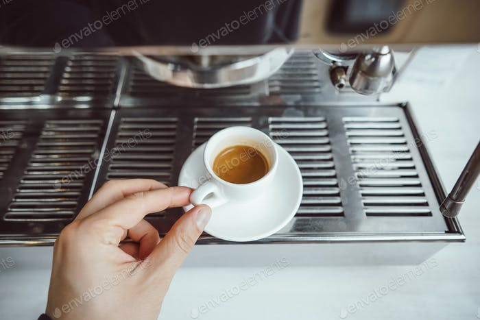 close-up view of glass cup with cappuccino and coffee machine