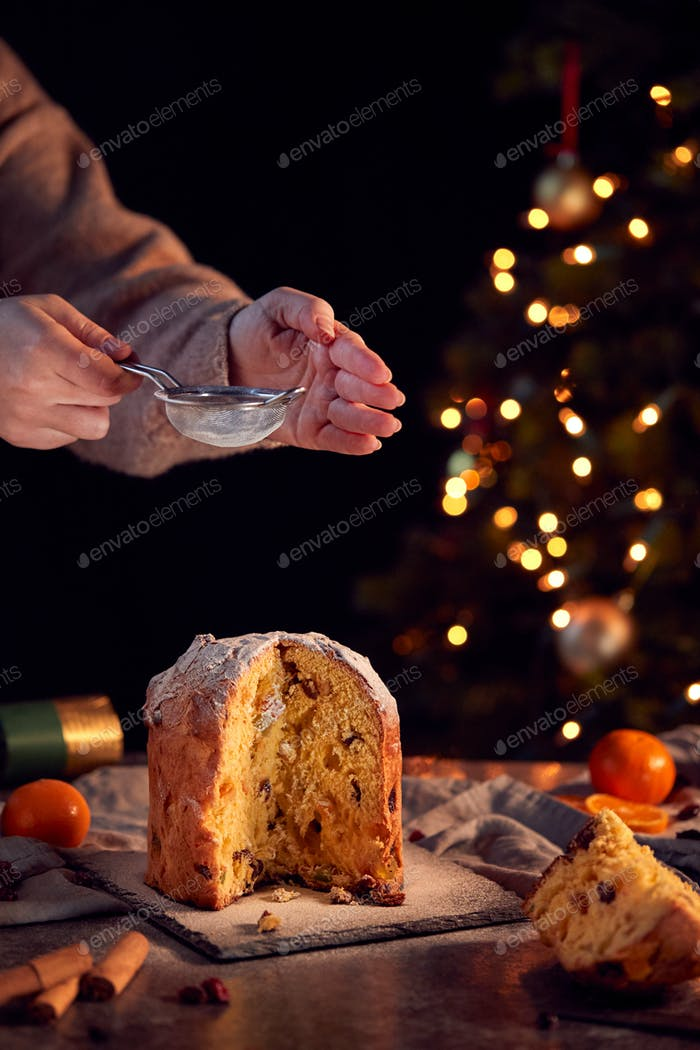Hand Shaking Icing Sugar Over Christmas Panettone On Table Set For Meal With Tree Lights Behind