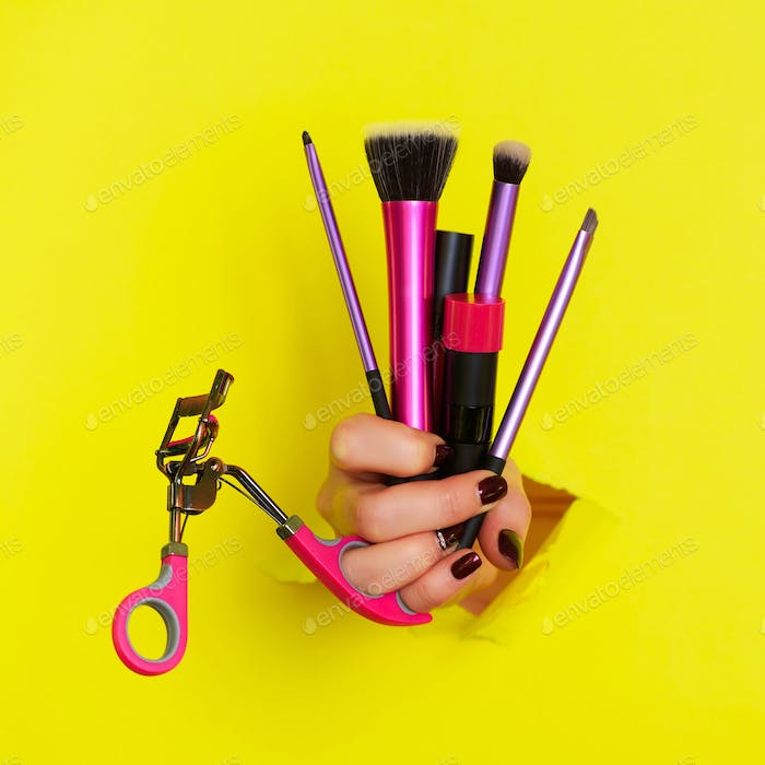 Woman hand with professional cosmetic tools for make up: brushes, mascara, lipstick, eyelash curler