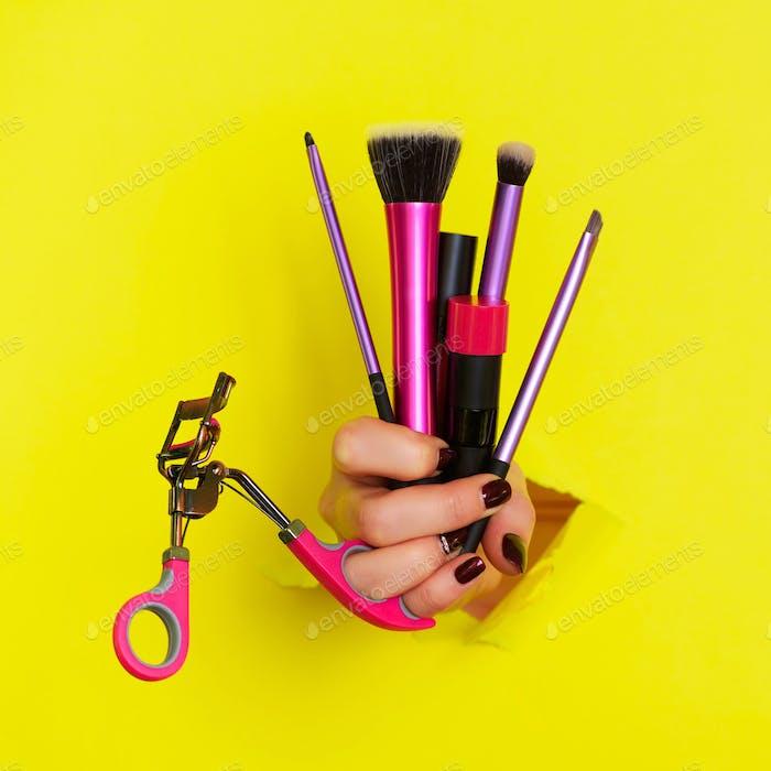 Frau Hand mit professionellen kosmetischen Tools für Make-up: Pinsel, Mascara, Lippenstift, Wimpernzange