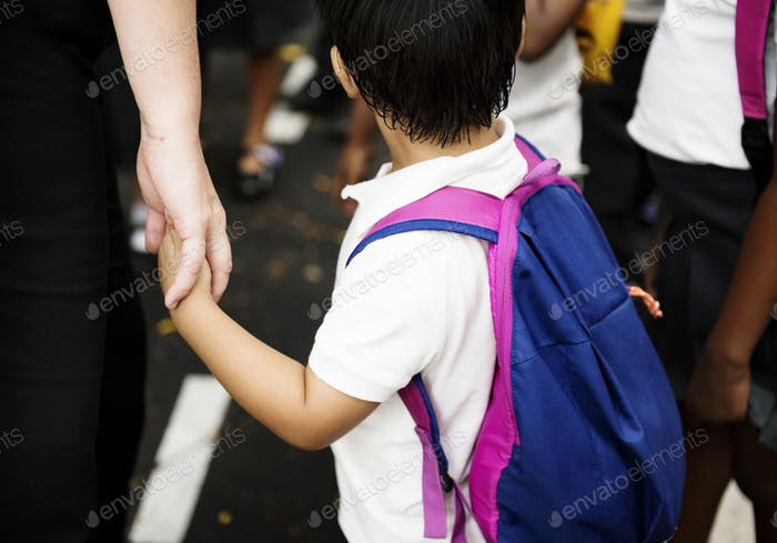 Kindergarten student holding hands with adult