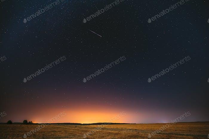 Natural Night Starry Sky Above Field Meadow. Glowing Stars, Mete