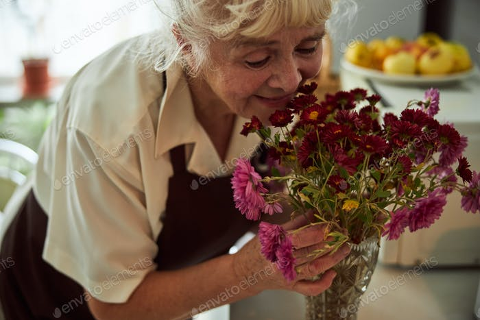 Joyful old woman smelling flowers at home