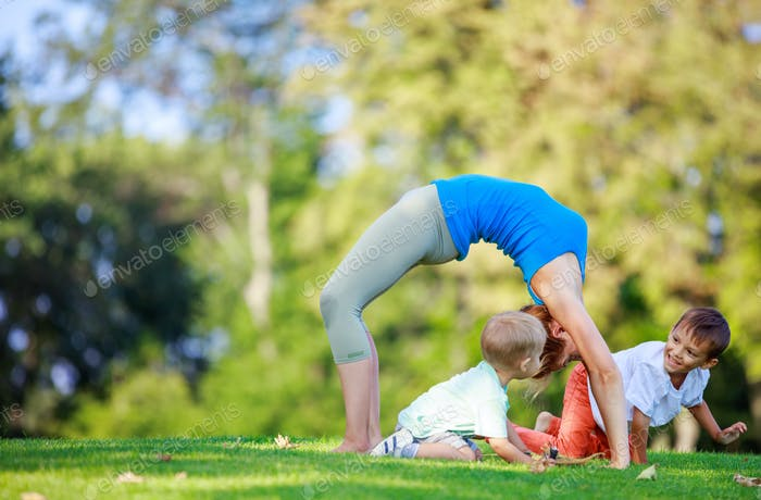 Young woman working out outdoors, little sons playing beside her
