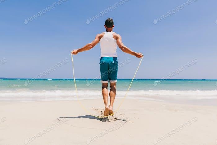 Fitness Mann überspringen auf dem Strand