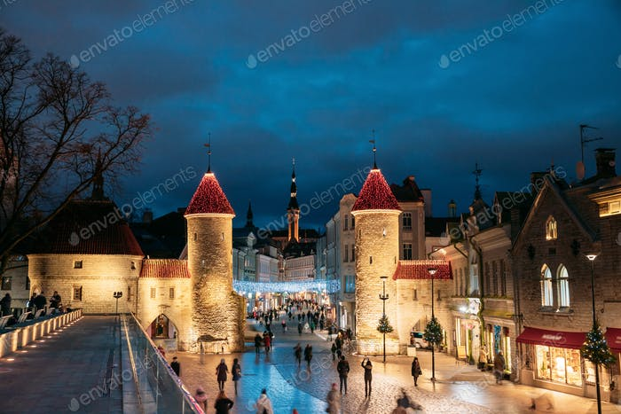 Tallinn, Estonia. People Walking Near Famous Landmark Viru Gate In Street Lighting At Evening Or