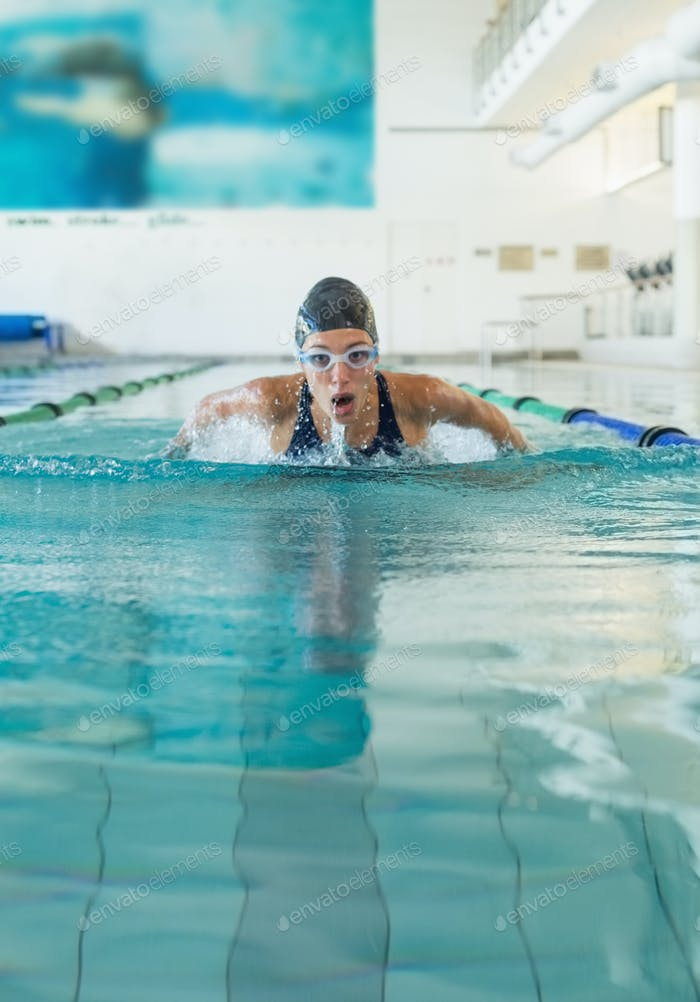 Fit swimmer doing the butterfly stroke in the swimming pool at the leisure center