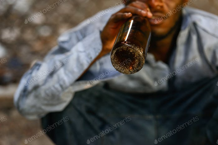 Hands of depressed young homeless African man drinking beer