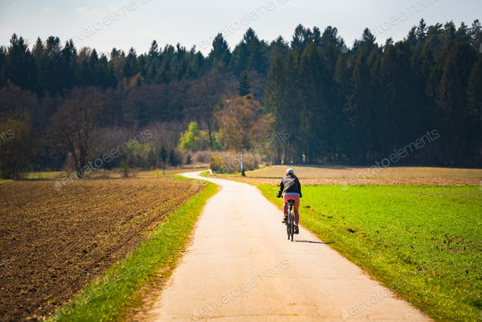 Girl riding a bike on rural road leading to forest