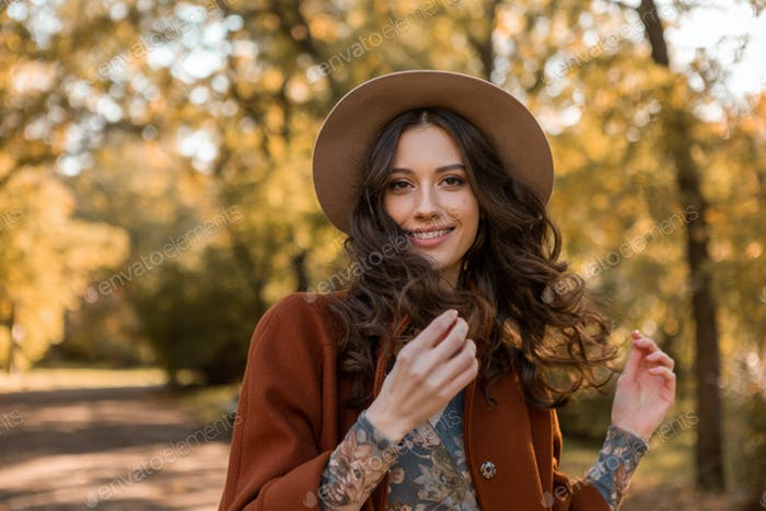 attractive stylish woman walking in park dressed in warm brown coat